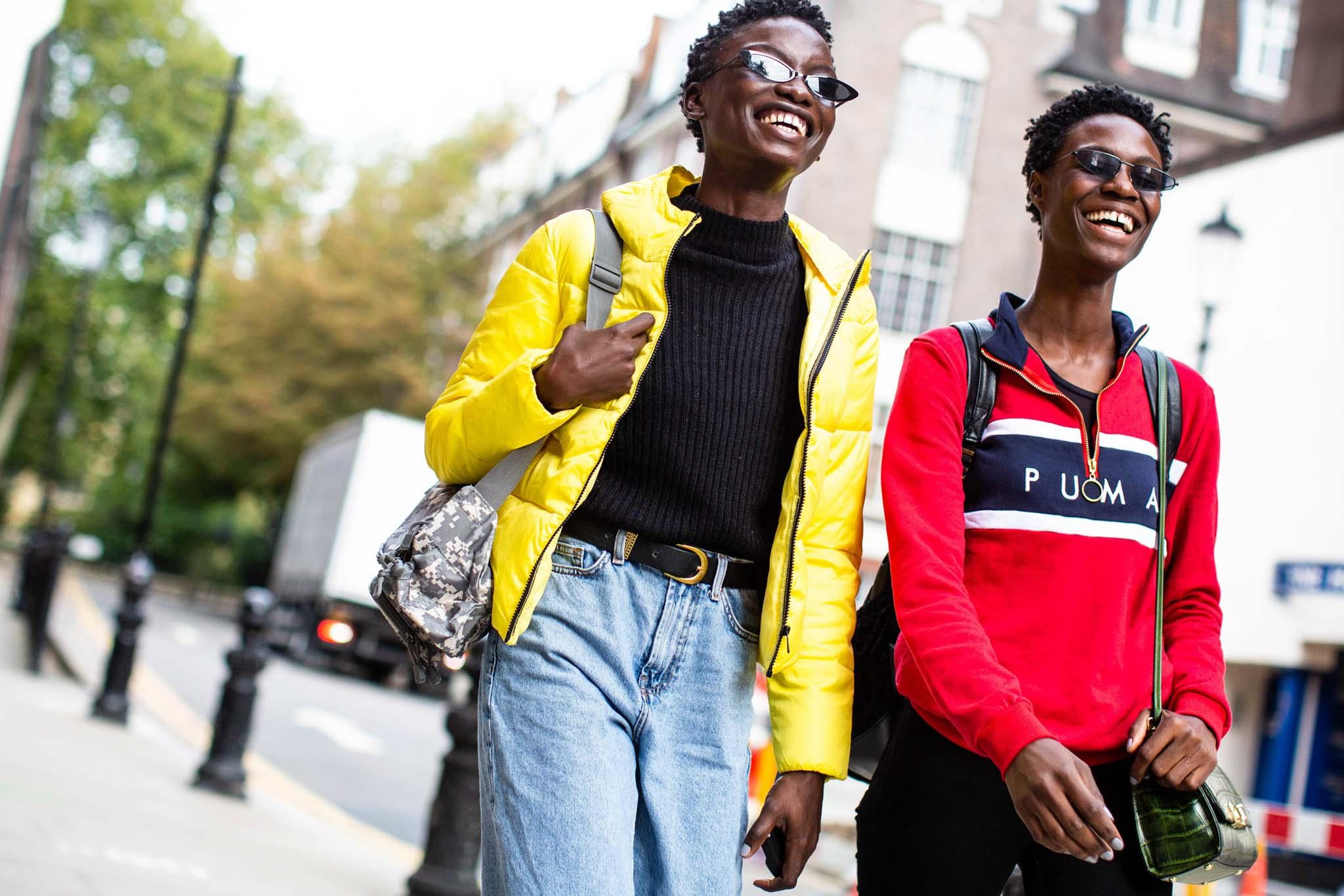 Cheveux noirs courts : deux femmes noires avec des torsades courtes marchant dans la rue lors de la semaine de la mode à Londres.