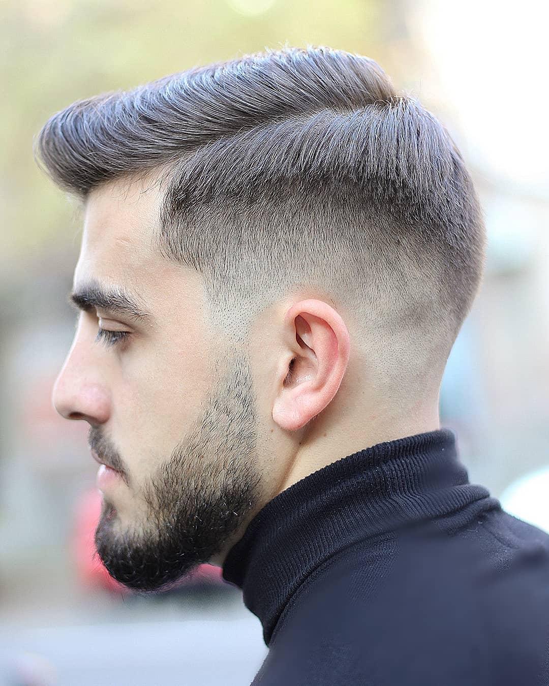 Homme aux cheveux bruns coiffés en peigne avec un dégradé bas.