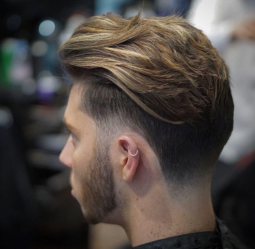 Homme aux cheveux bruns texturés de longueur moyenne avec une sous-coupe et une barbe.