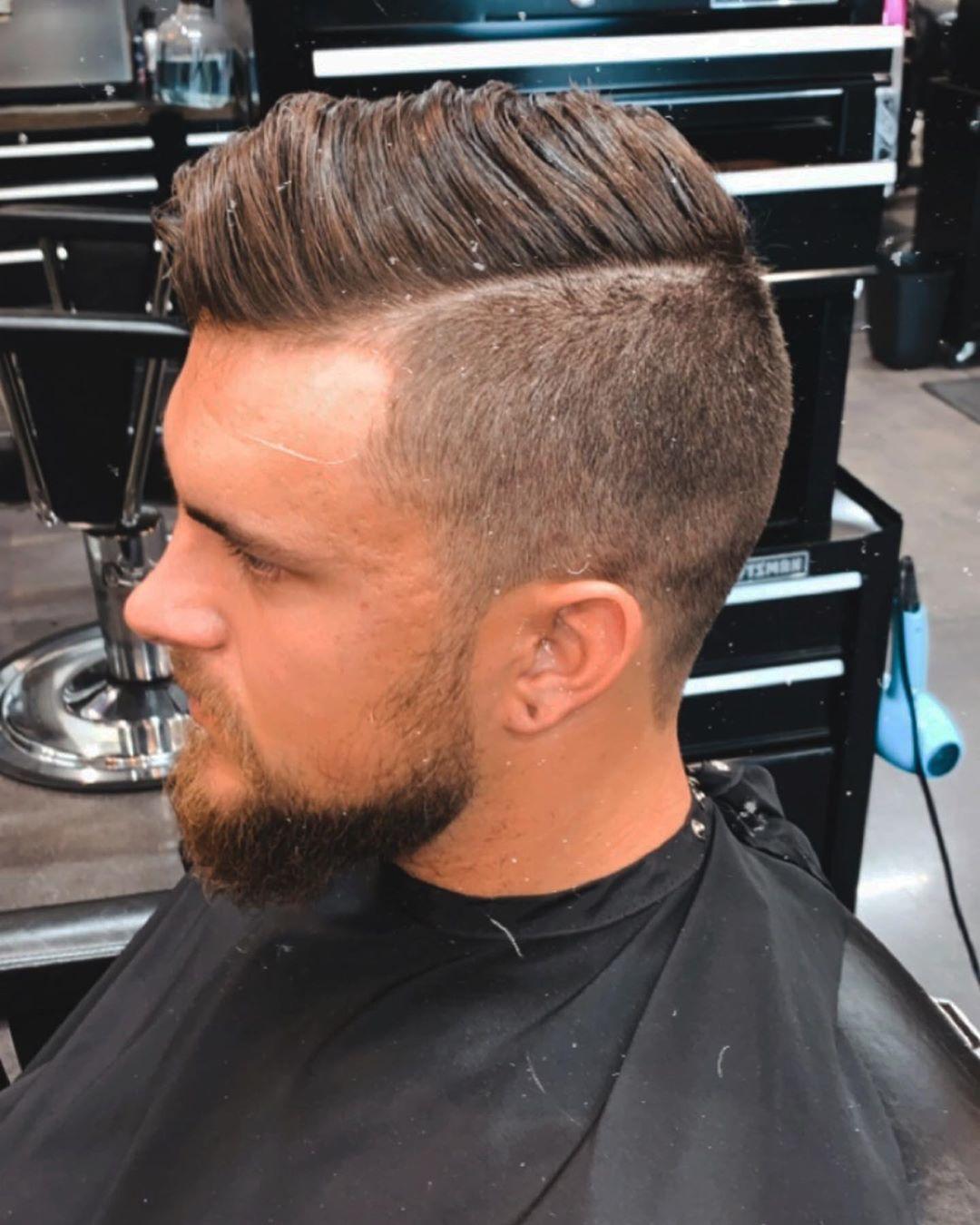 Homme aux cheveux bruns avec un peigne et une sous-coupe.