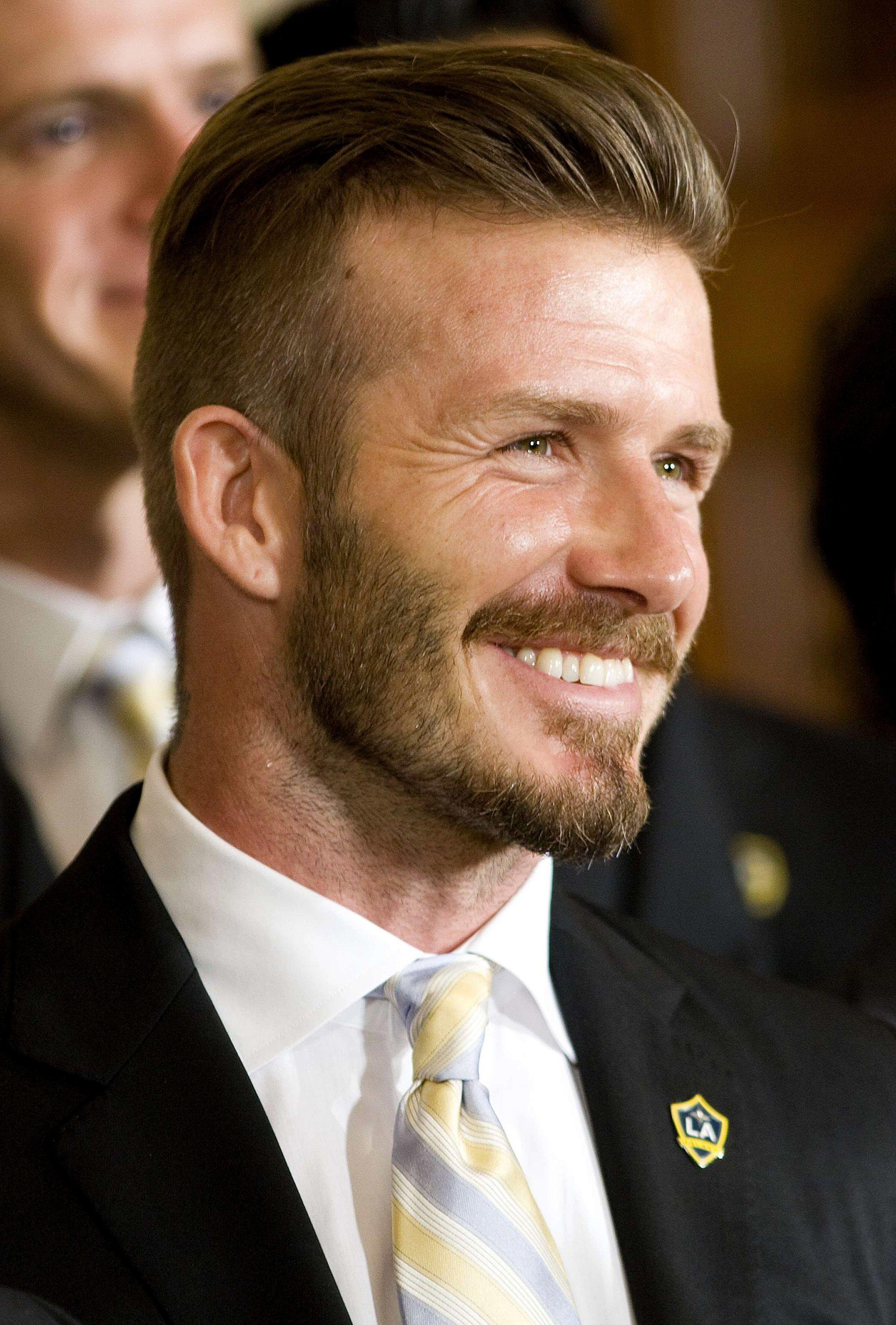 David Beckham avec des cheveux balayés en arrière avec une sous-coupe et une barbe.