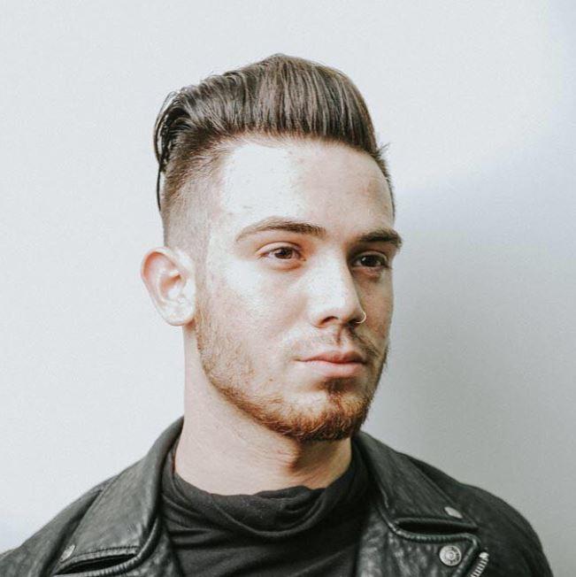 Vue de face d'un homme aux cheveux bruns avec une coupe courte en arrière.