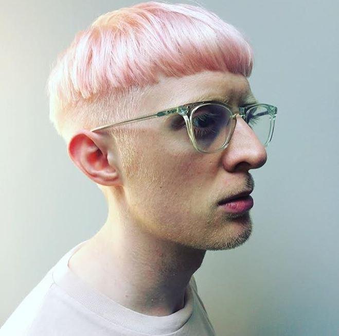 Vue de côté d'une coupe de cheveux rose pastel sur un homme à lunettes.