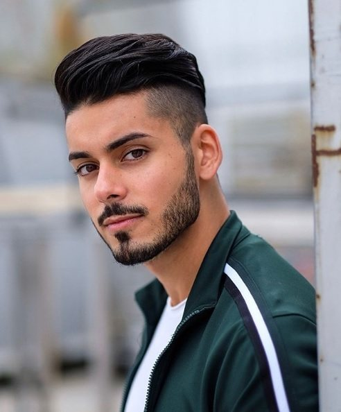 Street style shot of a man with brown hair in a slick pompadour style with an undercut