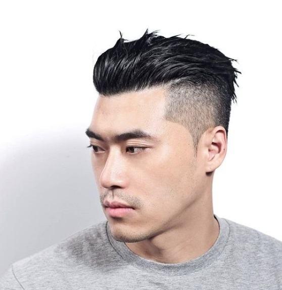 Homme aux cheveux bruns foncés gominés avec une sous-coupe, portant un t-shirt gris.