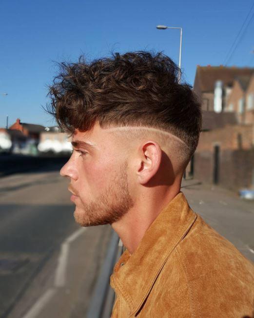 Vue de côté d'un modèle masculin aux cheveux bruns bouclés avec une coupe chirurgicale.