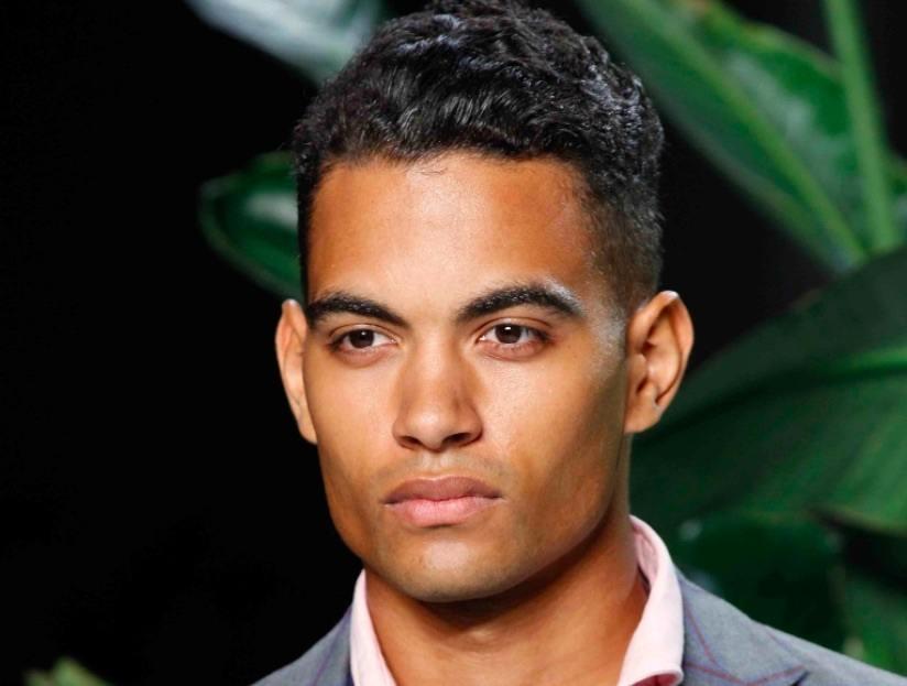 Vue de face d'un homme aux cheveux noirs ondulés et à la coupe courte.