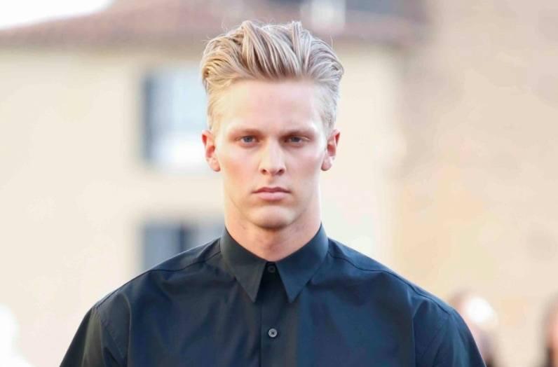 Vue de face d'un homme aux cheveux blonds, avec une touffe et une sous-coupe.