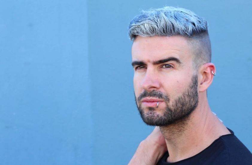 Vue de face d'un homme aux cheveux colorés et à la barbe.