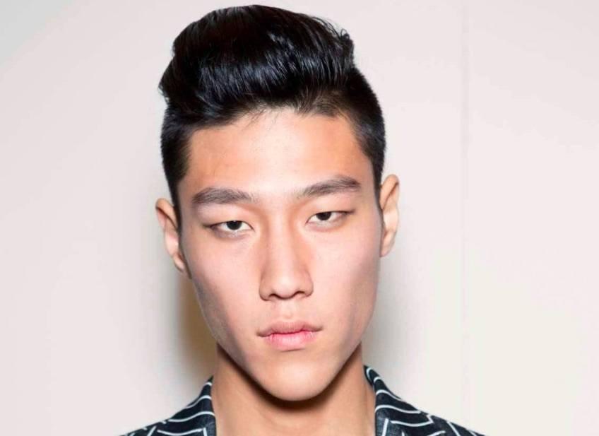 Image de face d'un homme avec des cheveux noirs au look mouillé, avec une sous-coupe et une touffe.