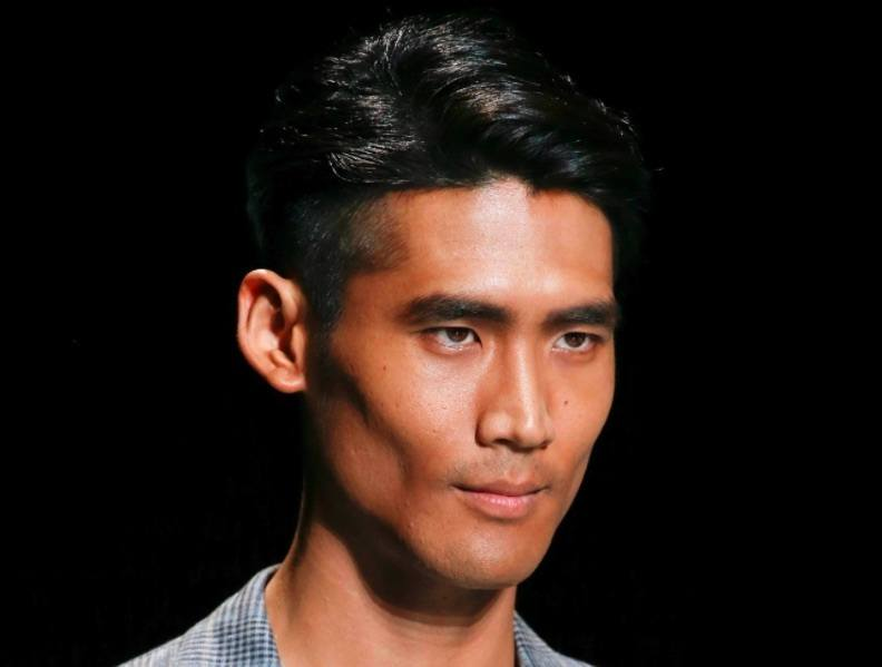 Image de face d'un homme aux cheveux noirs, avec une coupe courte et une raie sur le côté.
