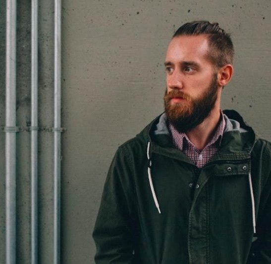 Vue de face d'un homme avec un chignon d'homme barbu et une sous-coupe.