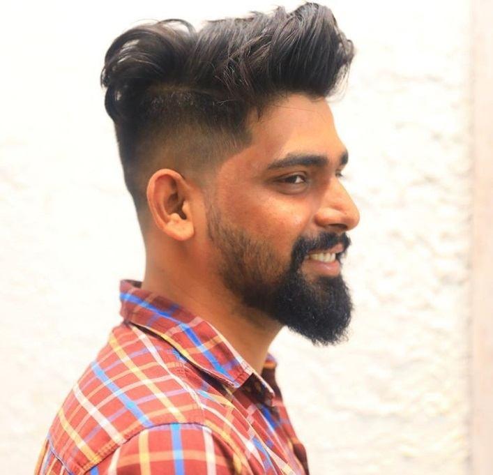 photo d'un modèle masculin portant un costume avec une coupe de cheveux bouclée sur le côté.