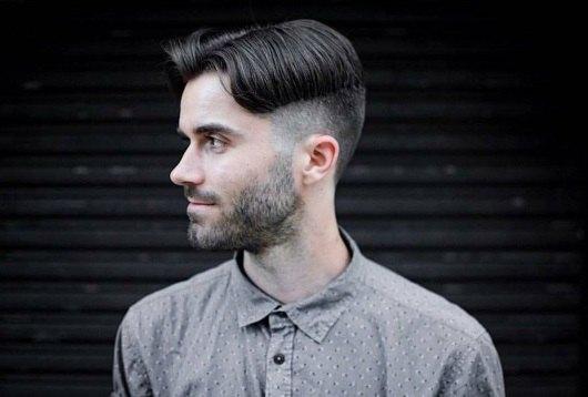 Plan de profil d'un homme brun avec des cheveux en rideau et une sous-coupe.