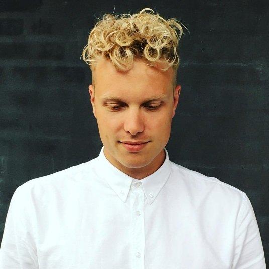homme blond avec des cheveux bouclés et une sous-coupe détail