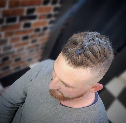 Vue d'oiseau d'un homme avec une coiffure tressée avec une coupe courte.