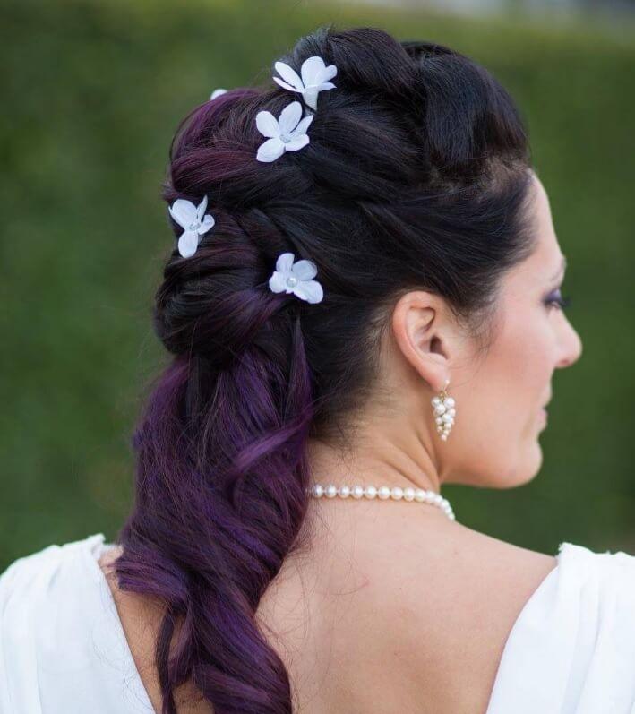 Femme avec des cheveux violets ombragés dans un tissage avec des fleurs ajoutées.