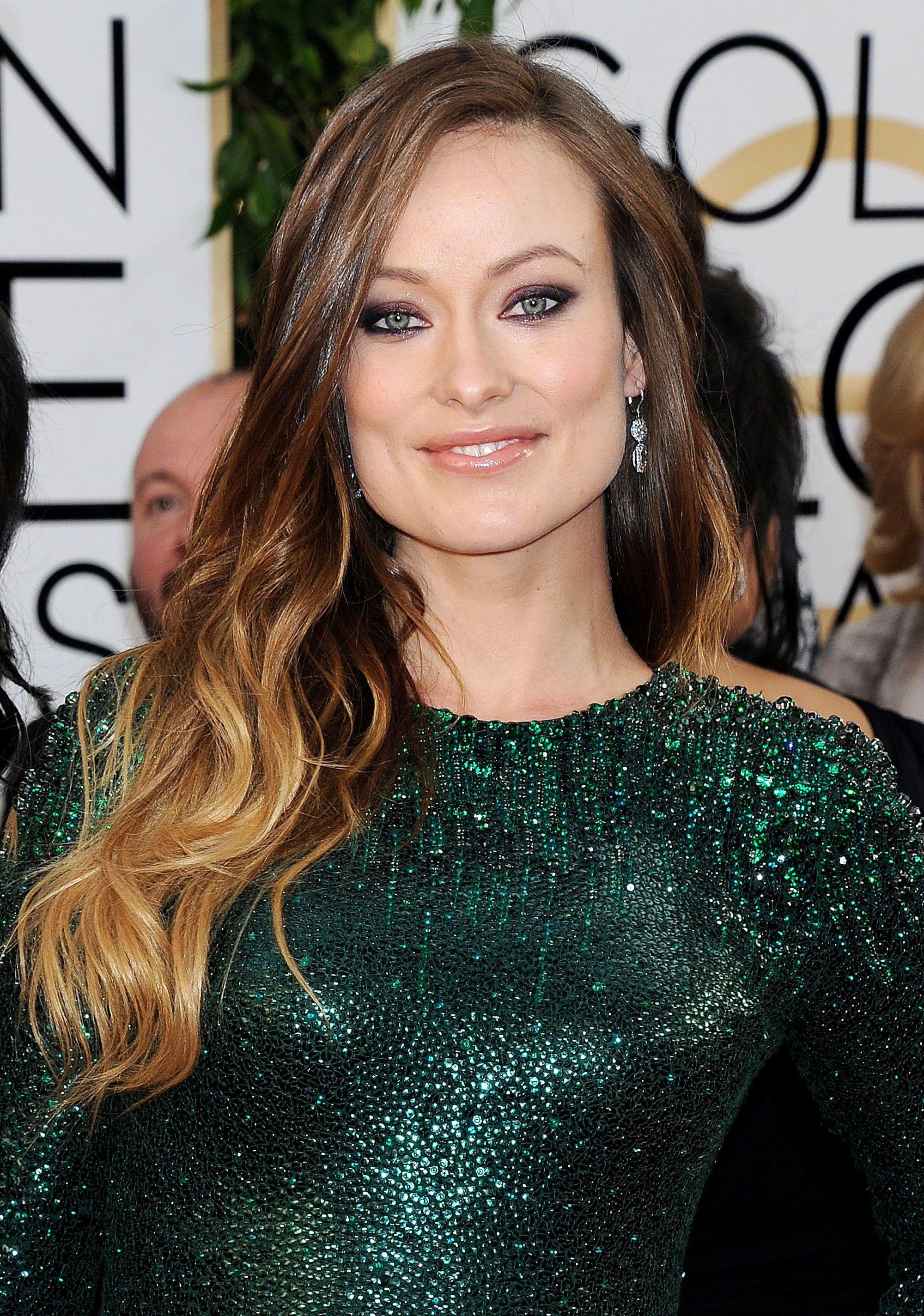 Olivia Wilde avec des cheveux longs et bouclés, d'un brun doré chaud et ombragé.