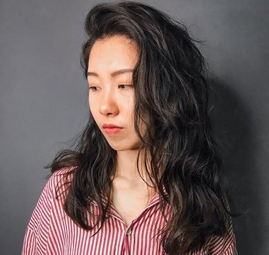 Permanente lâche : Plan rapproché d'une femme aux cheveux bruns foncés, avec des cheveux ondulés et lâches, coiffés sur le côté.