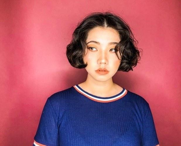 Permanente lâche : Plan rapproché d'une femme avec une coiffure permanente lâche de type bob à longueur de menton.
