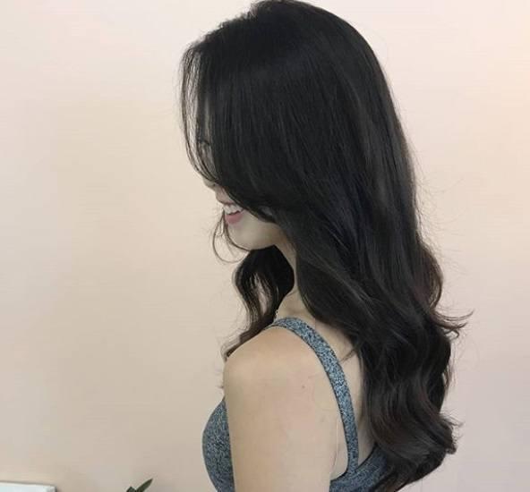 Permanente lâche : Plan rapproché d'une femme avec une longue chevelure brune dégradée à permanente libre.
