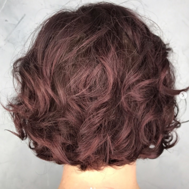 Vue de dos d'une femme avec une coupe de cheveux dégradée avec permanente lâche dans un salon de coiffure.