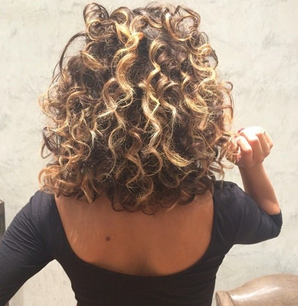photo de dos d'une femme avec une coiffure permanente à boucles lâches.