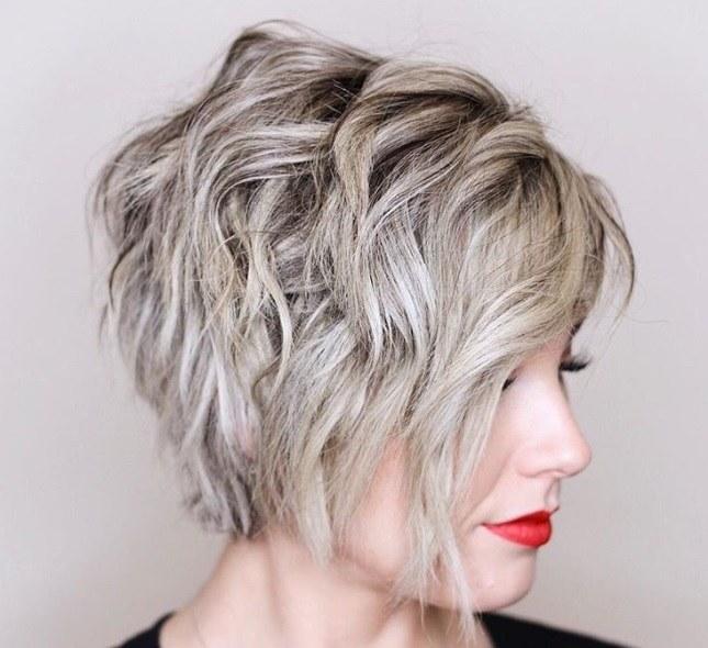 Permanente lâche : Plan rapproché d'une femme avec une coupe pixie blonde lâche avec permanente.