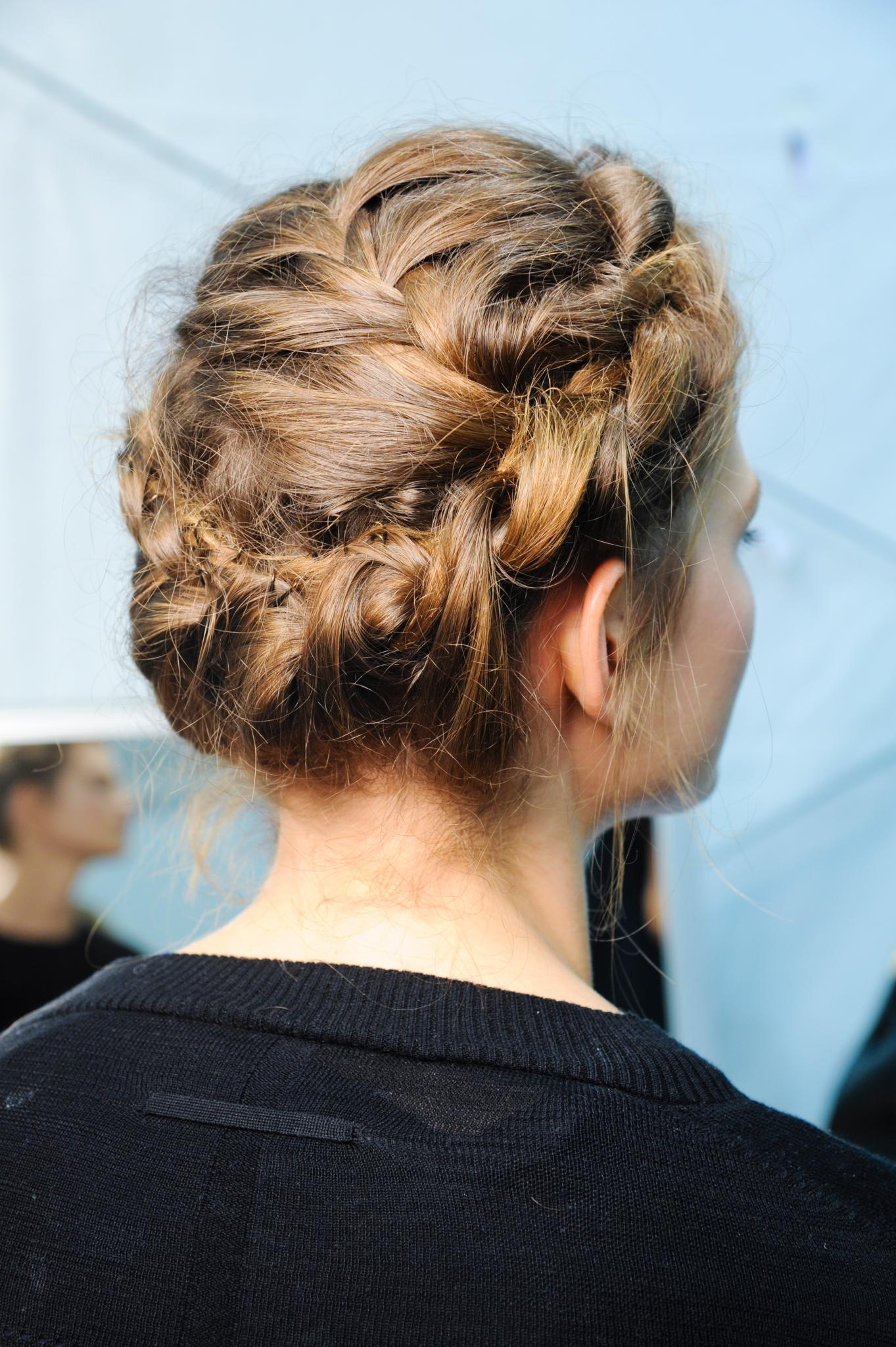 Plan de côté d'une femme avec des cheveux bruns moyens coiffés en couronne, portant un haut noir et posant dans les coulisses.
