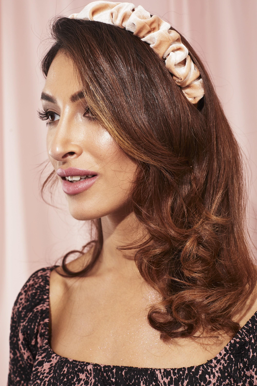 Femme avec des cheveux ondulés aux épaules avec un bandeau en satin rose froncé.