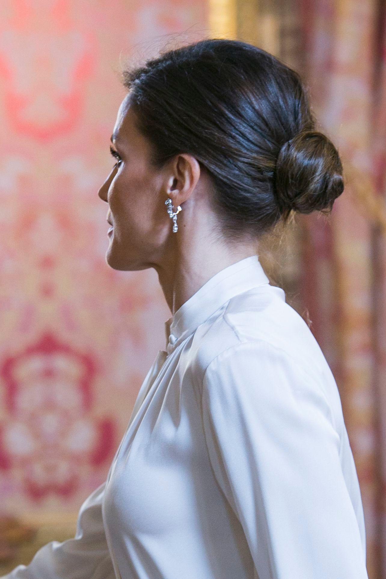 Coiffure d'une invitée de mariage : Plan de côté d'une femme aux cheveux châtain foncé coiffés en un chignon bas et poli, portant un chemisier blanc.