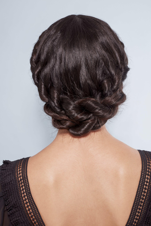 Plan arrière d'une femme aux cheveux bruns foncés coiffés en une tresse couronne torsadée, vêtue de noir et posant dans le studio Poudre de Rose UK.