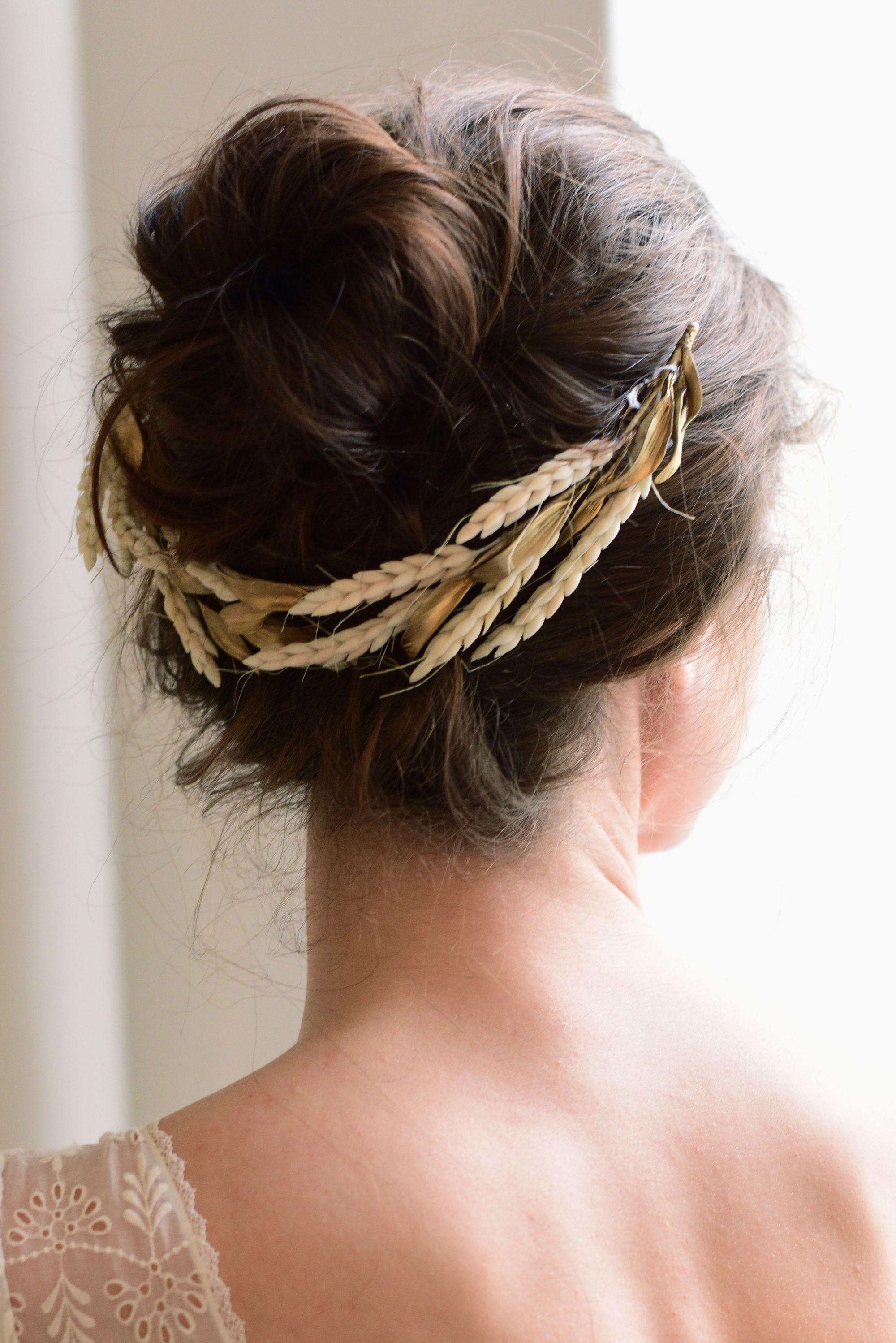 Coiffures d'invités de mariage : Plan arrière d'une femme aux cheveux châtain foncé coiffés en chignon avec un accessoire pour cheveux en forme de fleur dorée, posant dans une pièce éclairée.