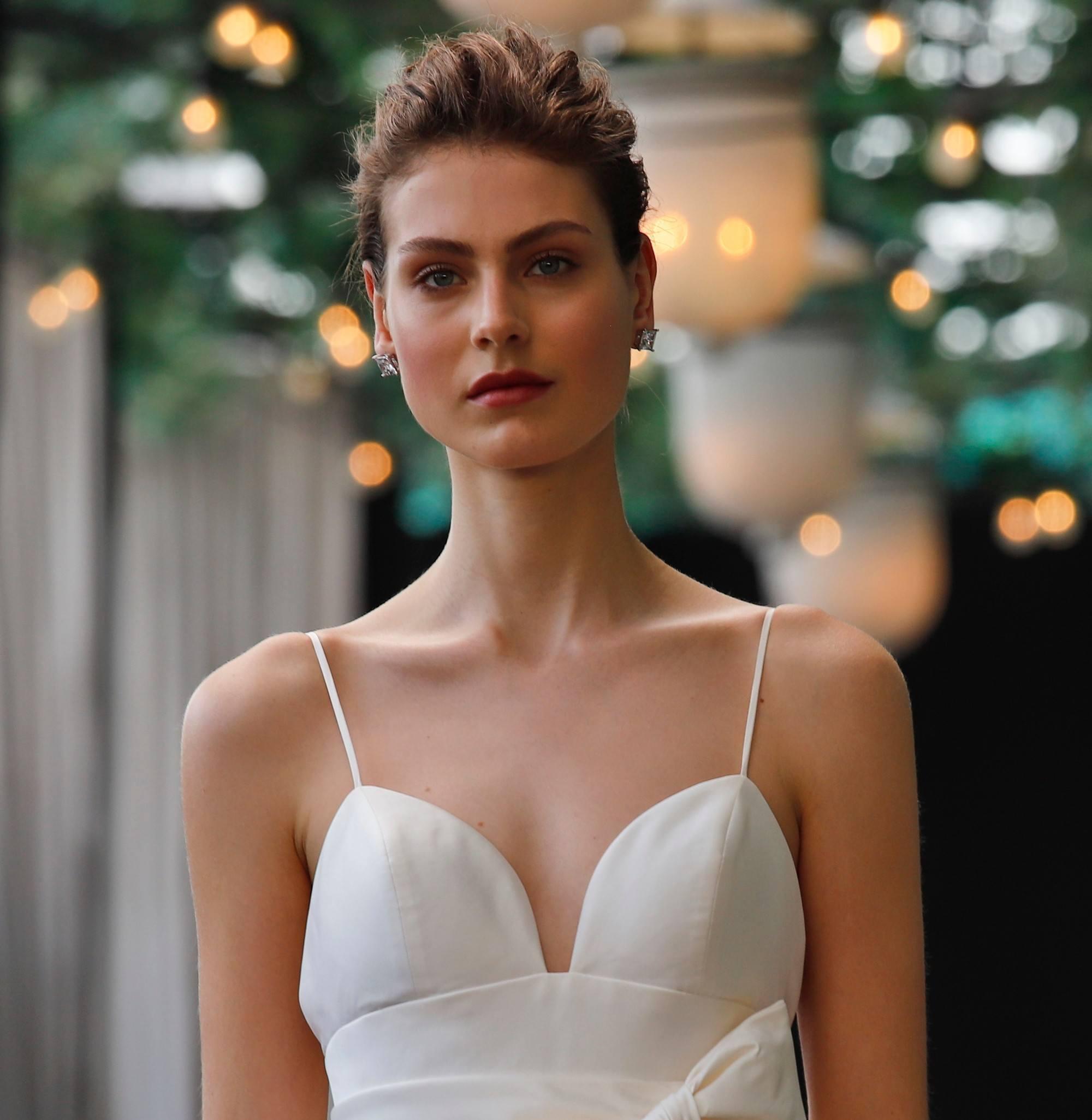 Prise de vue d'un mannequin sur un podium de mariage avec des cheveux courts coiffés en un quiff ébouriffé, balayé vers l'arrière, habillé tout en blanc.