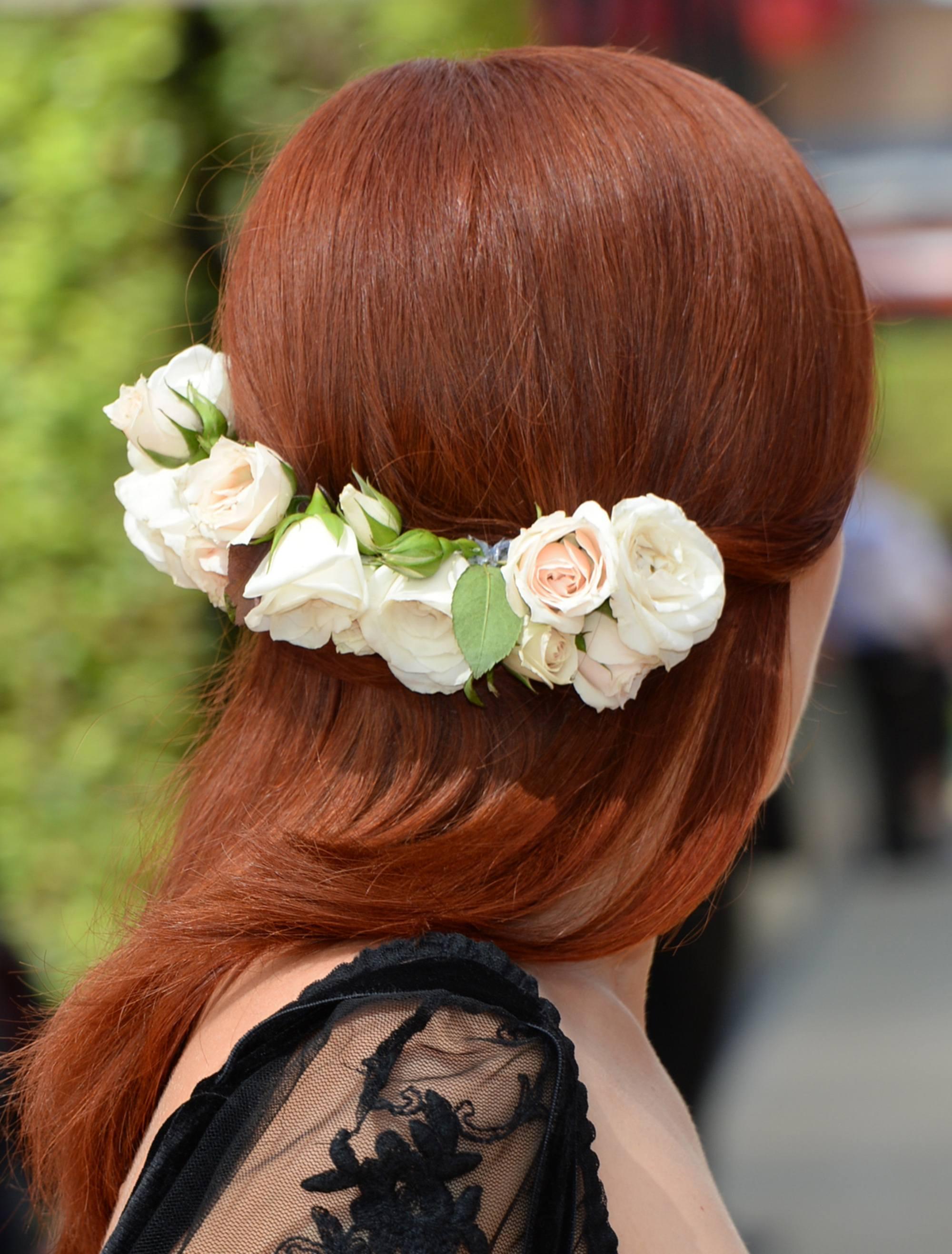 Coiffure d'une invitée de mariage : Plan arrière d'une femme aux cheveux roux cuivrés coiffés à la perfection, portant une épingle à cheveux basse à fleurs avec un haut en filet noir.