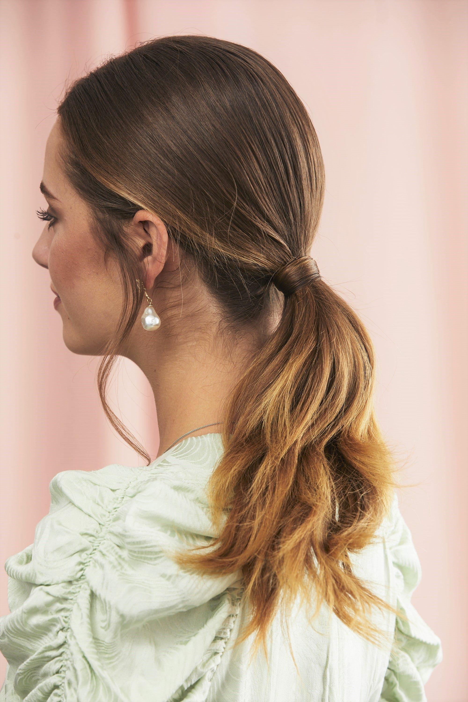 Femme aux cheveux châtain clair avec une queue de cheval basse et enroulée.