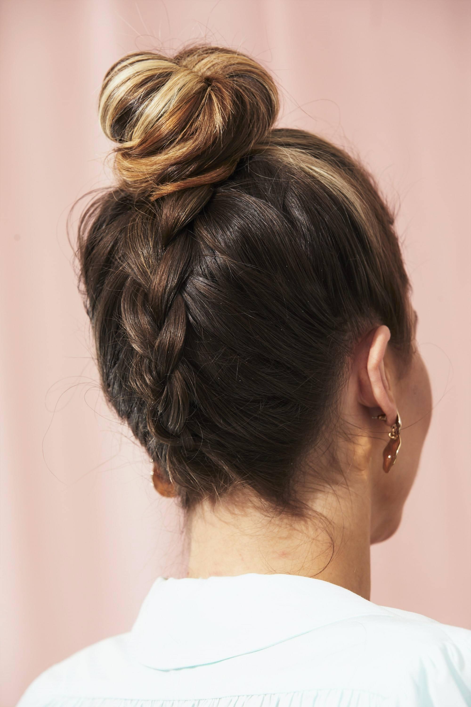 Femme aux cheveux bruns avec un chignon tressé à l'envers.