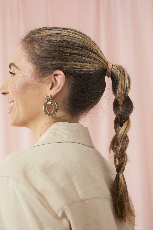 Femme aux cheveux bruns avec une queue de cheval tressée.