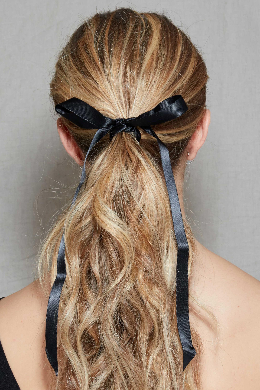 Coiffure d'une invitée de mariage : Plan arrière d'une femme aux longs cheveux blonds sales coiffés en queue de cheval avec un ruban attaché autour, posant dans le studio Poudre de Rose.
