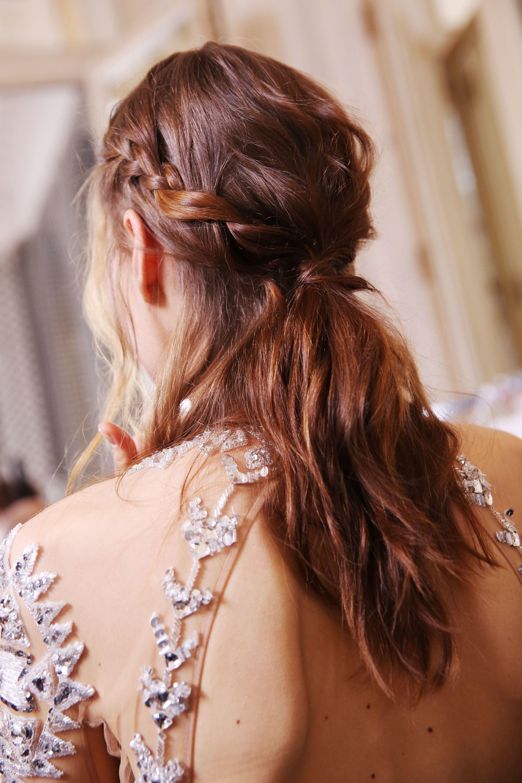 mannequin brune en coulisses portant une robe brodée transparente avec des cheveux tressés, mi-hauts mi-bas.