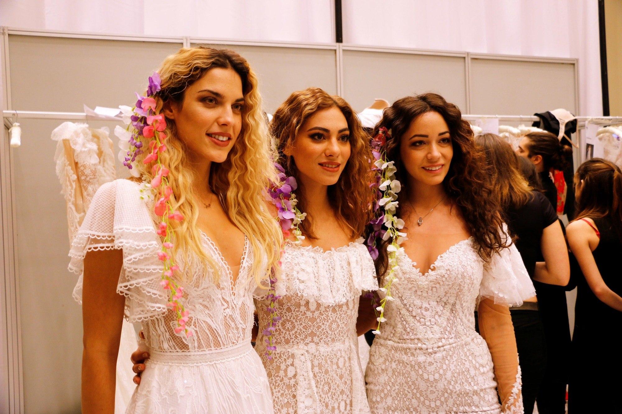 Coiffures d'invitées de mariage : Gros plan de trois femmes aux cheveux de plage bouclés et lâchés, portant du blanc et des fleurs dans les cheveux.