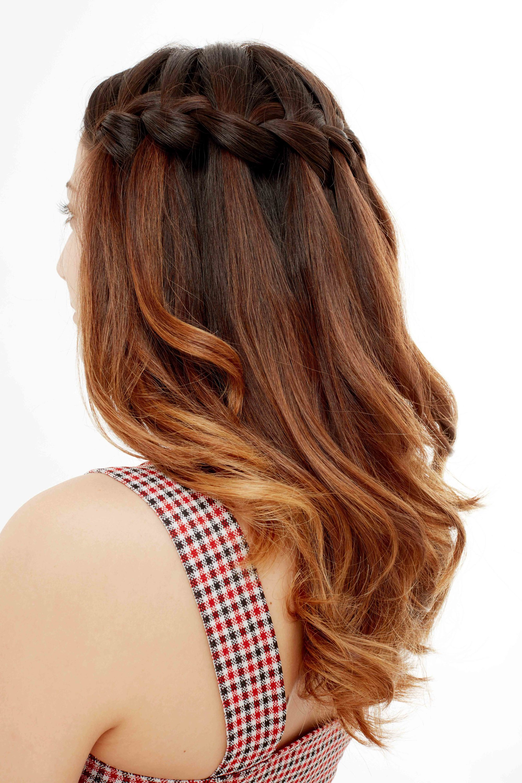 Plan de côté d'un mannequin avec des cheveux moyens ondulés de couleur brune à rouge, coiffés en une tresse en cascade, posant dans le studio Poudre de Rose UK.