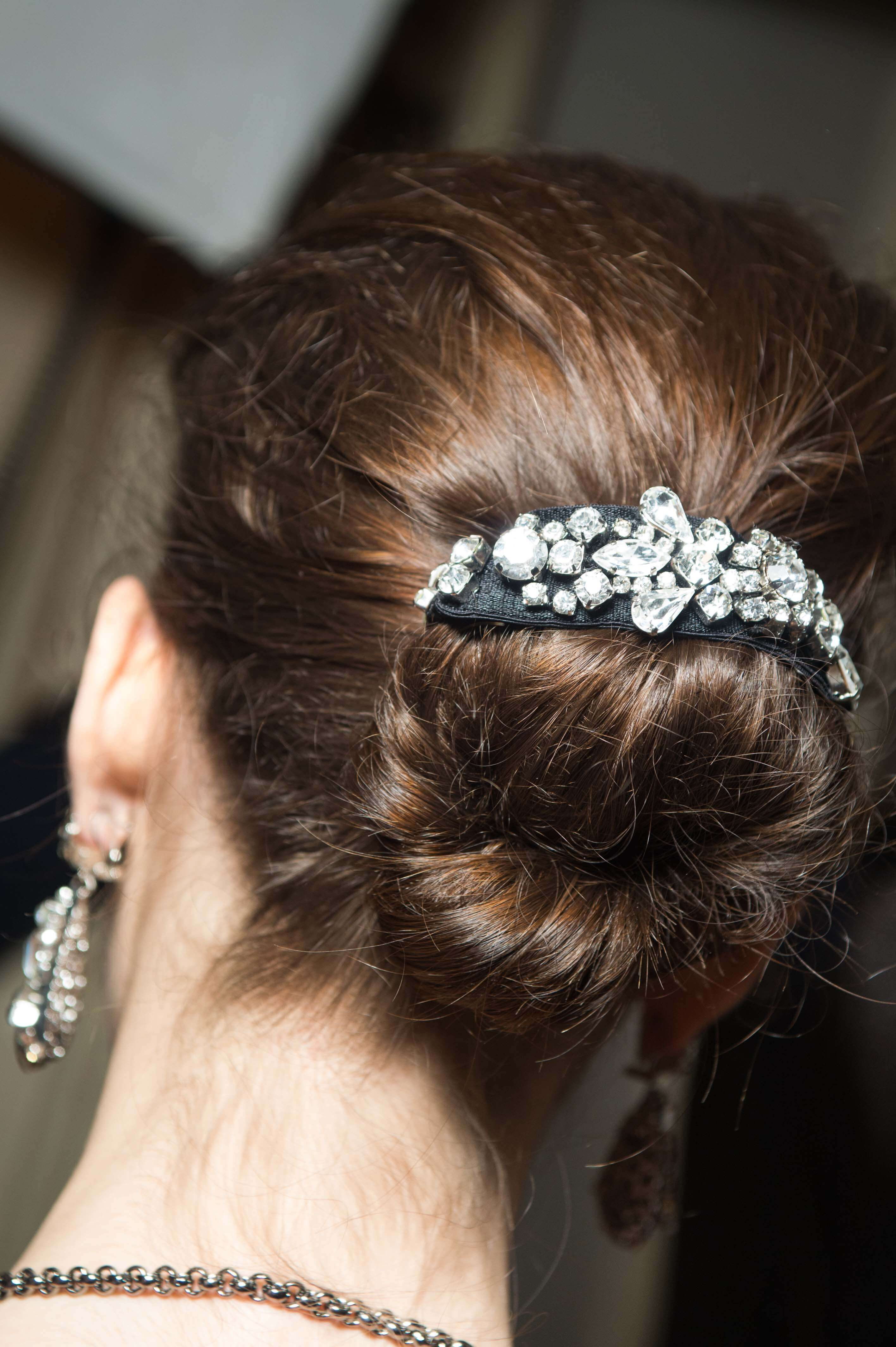vue de dos d'une brune avec ses cheveux en chignon désordonné avec une manchette de chignon à bijoux