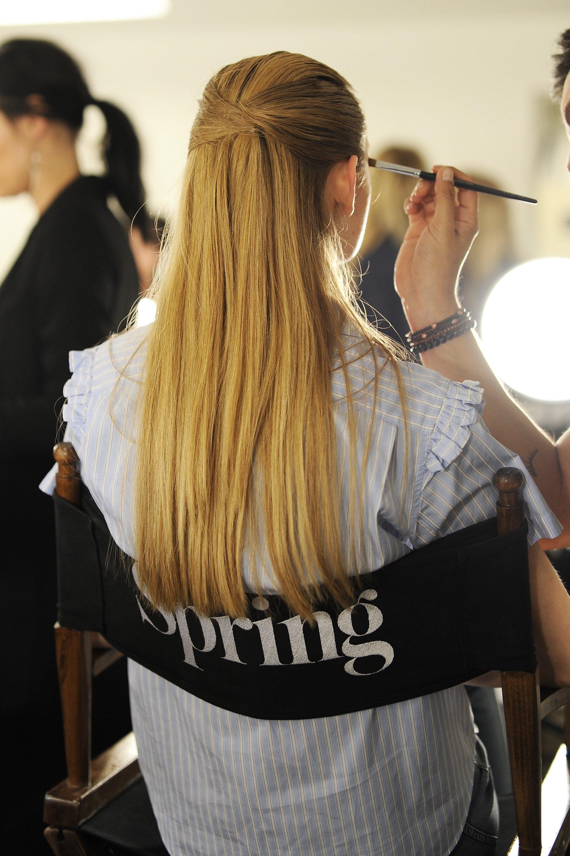 mannequin dans les coulisses avec des cheveux blonds foncés et lisses dans une coiffure pliée, moitié haute, moitié basse.