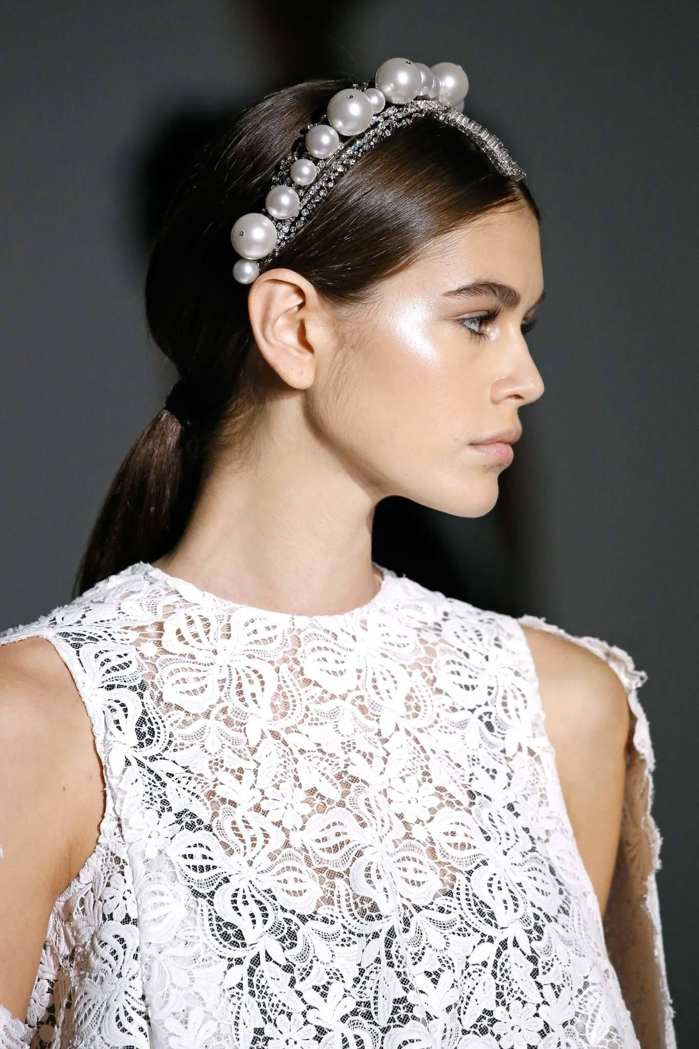 Coiffure d'une invitée de mariage : Prise de vue d'un mannequin aux longs cheveux châtain foncé coiffés en queue de cheval lisse, portant un serre-tête en perles sur le podium.