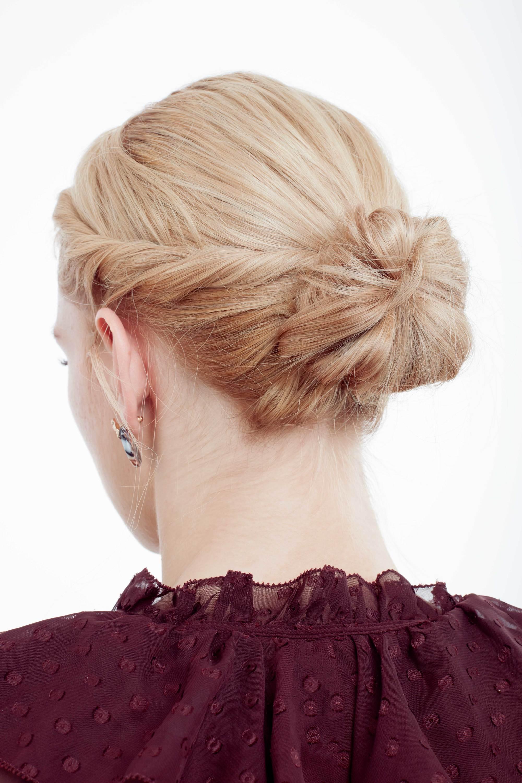Coiffure d'une invitée de mariage : Plan arrière d'un mannequin aux cheveux blonds dorés coiffés en un chignon torsadé bas, portant un haut violet à volants dans le studio Poudre de Rose UK.