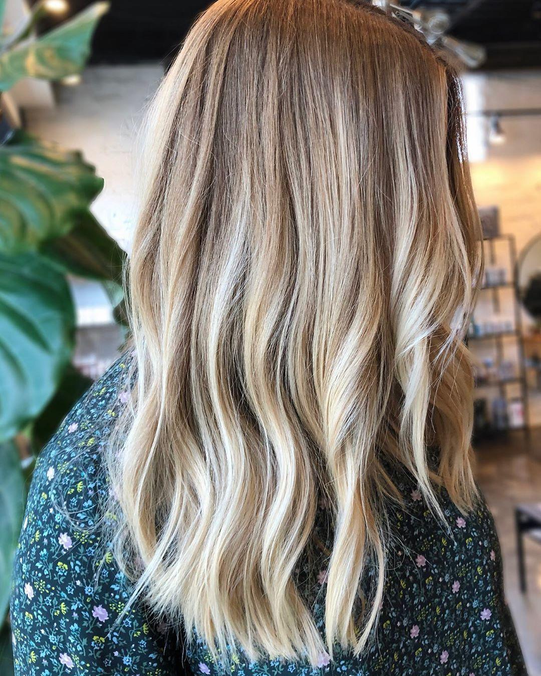 Femme avec des cheveux mi-longs ondulés blond miel avec des mèches blond clair.