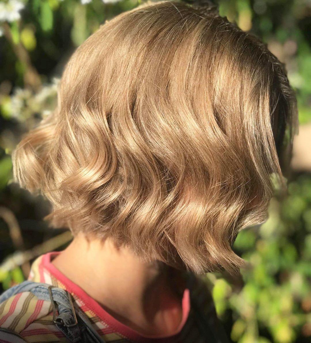 Femme avec une coupe courte ondulée blonde miel clair.