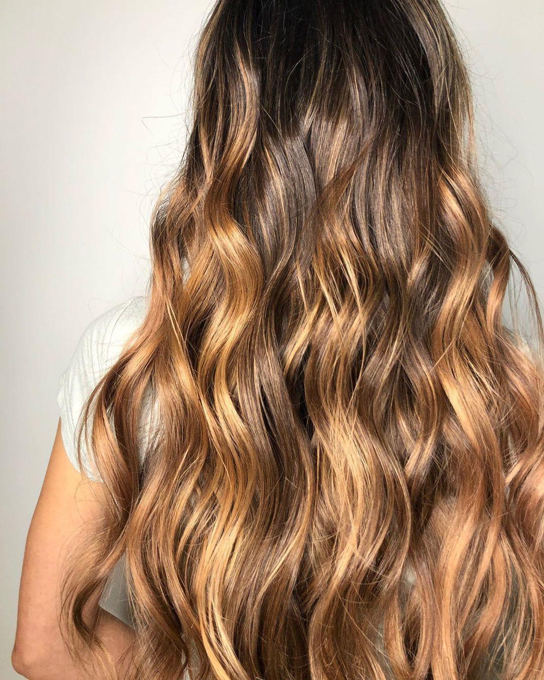 Femme avec de longs cheveux ondulés blond miel foncé