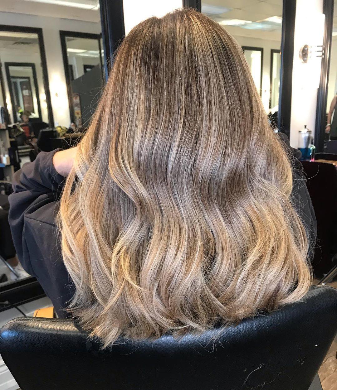 Femme avec des cheveux naturels blond miel ondulés mi-longs.